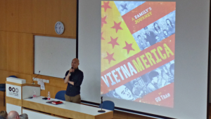 GB Tran giving a lecture and the cover page and title of his book behind him on the screen