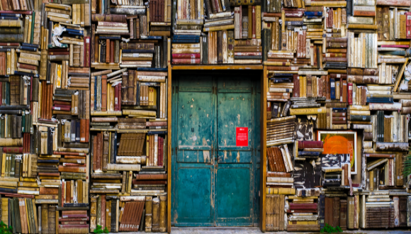 Blue wooden door in the wall painted as piles of books