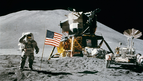 Astronaut standing on moon next to American flag and lunar module